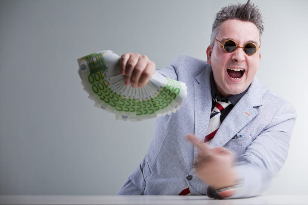 Man with sunglasses pointing to a handful of cash